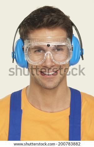 Man wearing ear muff and protective goggles smiling portrait - stock photo