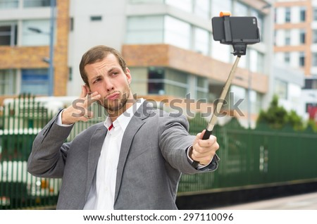 Man wearing formal clothing posing with selfie stick in urban environment using right hand to make a signal. - stock photo
