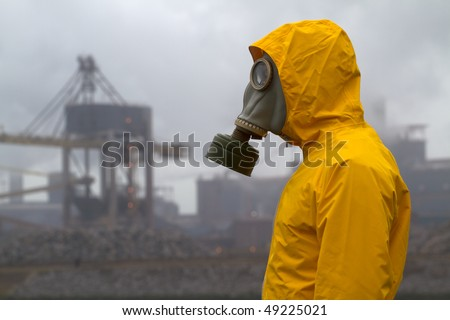 Man wearing gas mask standing infront of factory. Side shot. Background out of focus - stock photo
