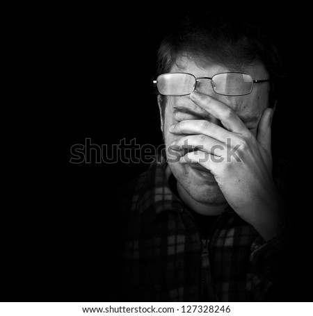 man wearing glasses with eye strain, frowning with hand on head black and white with copy space - stock photo