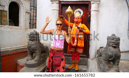Man wearing Hanuman costume and tourist girl - stock photo