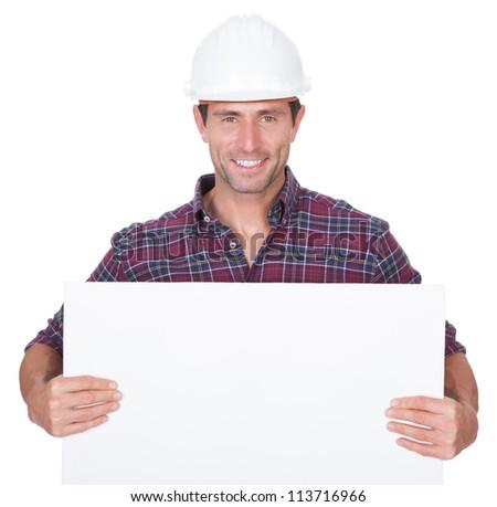 Man Wearing Hard Hat Holding Placard On White Background - stock photo