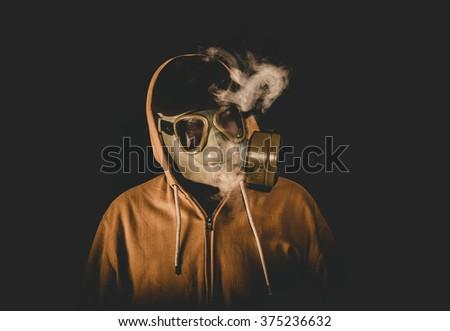 Man wearing mask and smoking,low key - stock photo