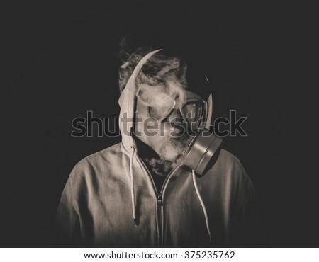 Man wearing mask and smoking,low key and monochrome - stock photo