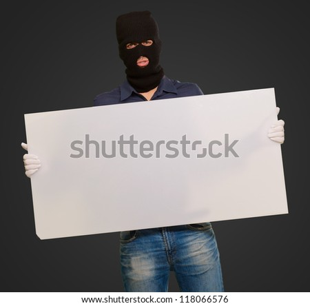 Man wearing mask holding a blank card isolated on black background