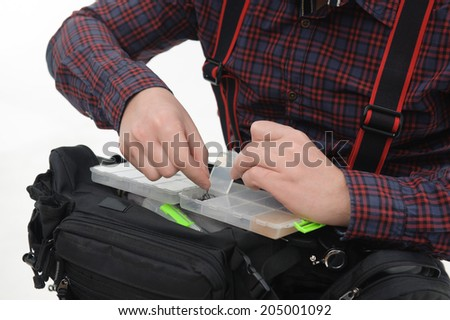 Man wearing nice checked shirt taking out fishing baits from the plastic box. Close up - stock photo