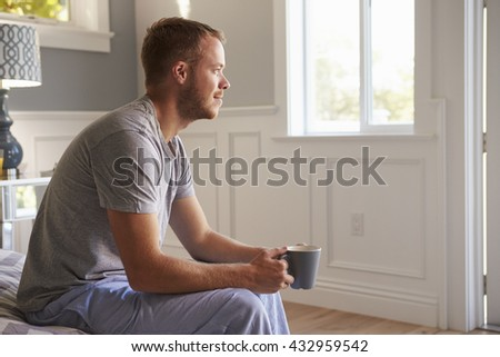 Man Wearing Pajamas Sitting On Bed With Hot Drink - stock photo
