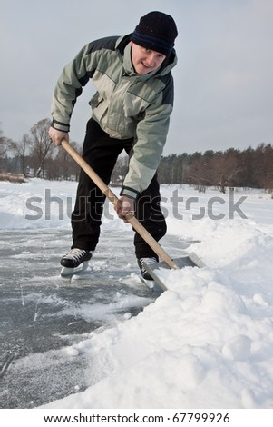 Man wearing skates working with snow shovel. - stock photo