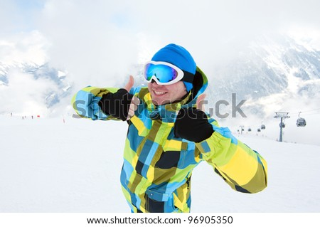 Man wearing ski equipment, smiling on slope with mountains background - stock photo