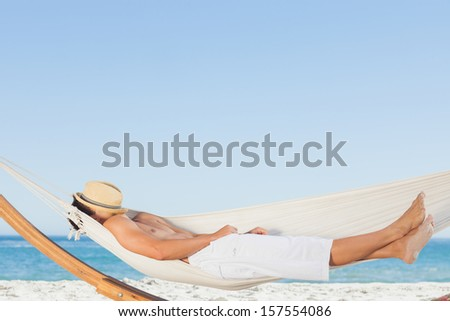 Man wearing straw hat relaxing in a hammock on the beach on holidays - stock photo
