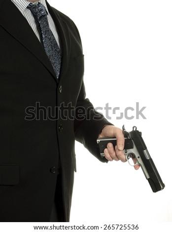 Man wearing suit and tie holding gun in hand. Standing, holding gun inspector, cop, police, policeman, indoor, crime - stock photo
