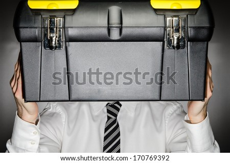 Man wearing tie holding toolbox in front of his face - stock photo
