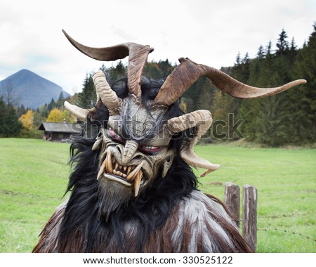 Man wearing traditional Krampus beast-like mask from Alpine region - stock photo