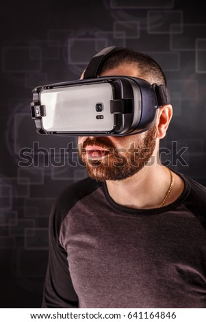 Man wearing virtual reality goggles, studio shot