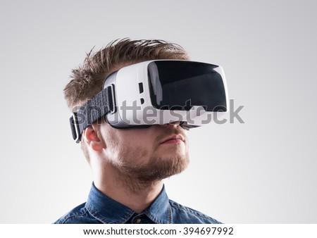 Man wearing virtual reality goggles. Studio shot, gray backgroun - stock photo
