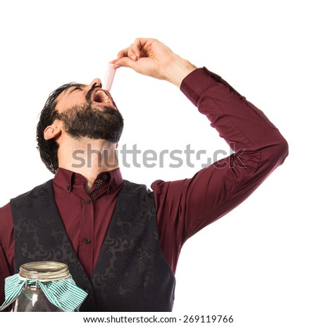 Man wearing waistcoat holding glass jar with sweets inside  - stock photo