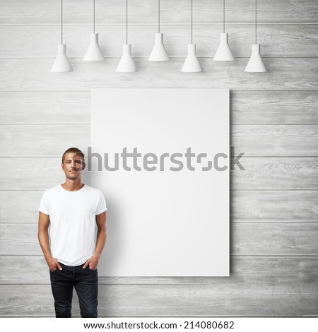 Man wearing white t-shirt and blank poster on a wall - stock photo