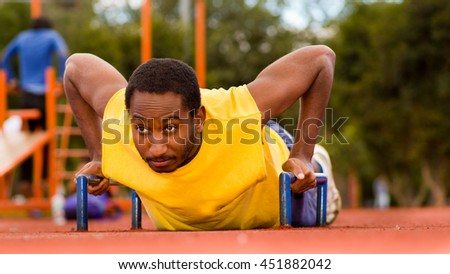 Man wearing yellow shirt doing push-ups at outdoors training facility, orange athletic surface and green trees background