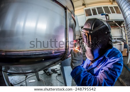 Man welding with reflection of sparks on visor. Hard job. Construction and manufacturing - stock photo