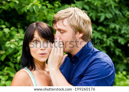 Man whispering into the woman's ear - stock photo