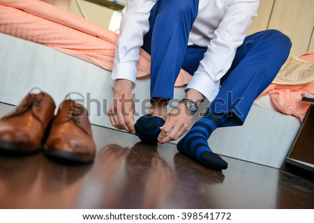Man who put his socks with shoes in front of him - stock photo