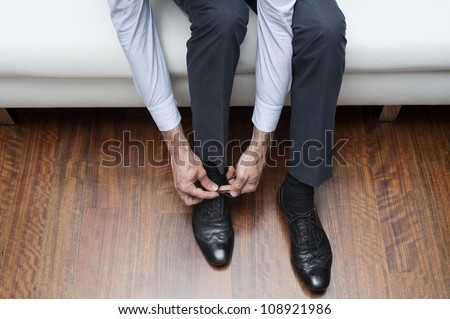 man who ties his black shoes - stock photo