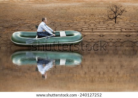 man will rows home for shore in paddle powered row boat businessman in boat rocks looks bright future symbol crisis stagnation losses braking difficulties environmental disaster water scarcity drought - stock photo