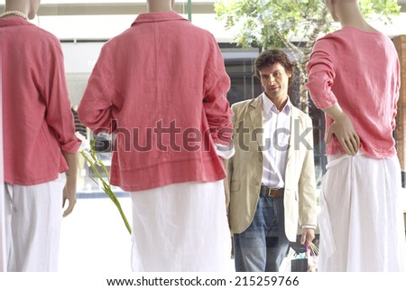 Man window shopping, looking at three mannequins wearing pink tops and white skirts in clothes shop - stock photo