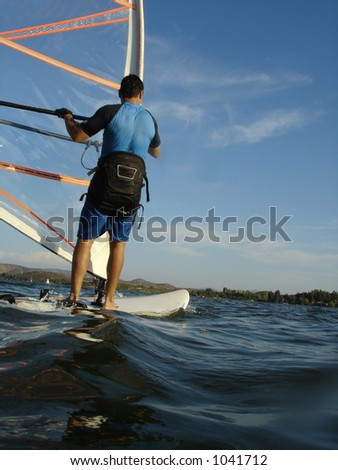 Man windsurfing in a lake on a sunny day
