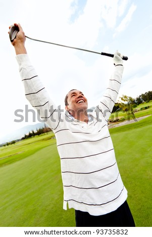 Man winning at golf with arms up at the course - stock photo