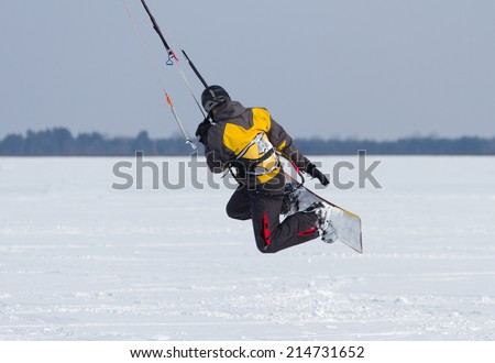 Man winter snowkiting on a frozen lake  - stock photo
