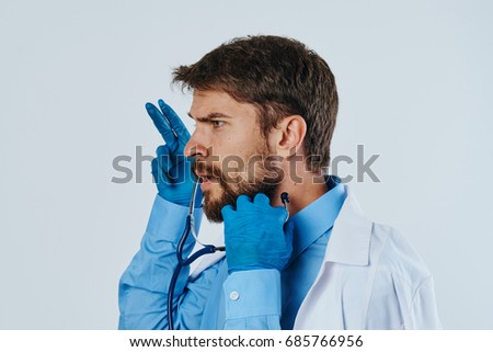 Man with a beard against a light background in a medical dressing gown, doctor, medicine.
