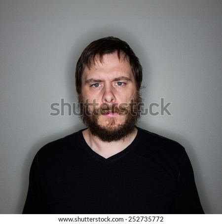 man with a beard and mustach looking at the camera. - stock photo