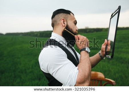 Man with a beard and sunglasses in the green field - stock photo