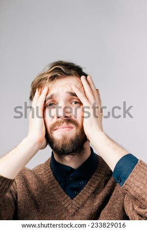 Man with a beard in brown sweater with hangover - stock photo