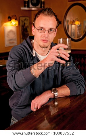 Man with a beer in bar giving a toast and smiling - stock photo
