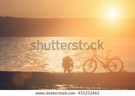 Man with a bicycle on the river at sunrise or sunset - stock photo