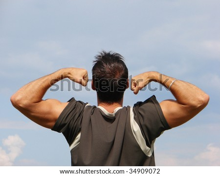 Man with a body builder on the background sky - stock photo