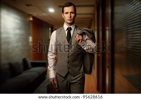 Man with a briefcase in a hotel hallway.