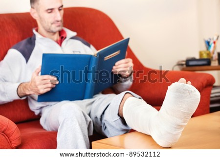 man with a broken leg on a sofa at home  reading book; focus on cast - stock photo