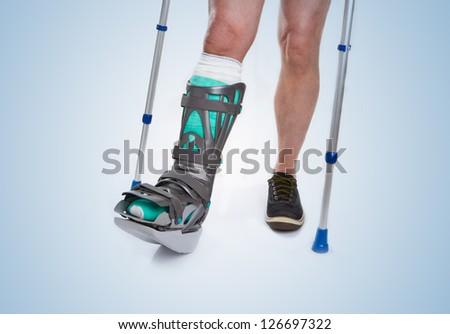 Man with a broken leg with Crutches and Orthotic on a blue background - stock photo