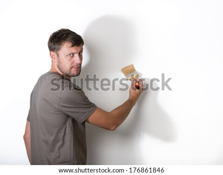 Man with a brush paints the white wall