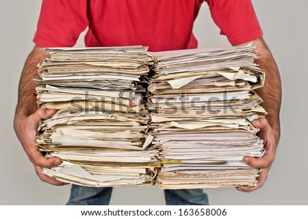 Man with a bunch of old newspapers in the hands - stock photo