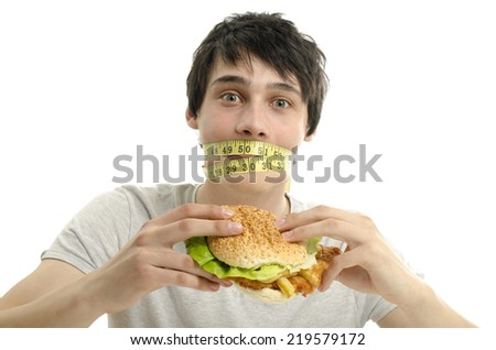 Man with a centimeter on his mouth unable to eat a big hamburger, young man dieting and having a hard time with fast food - stock photo