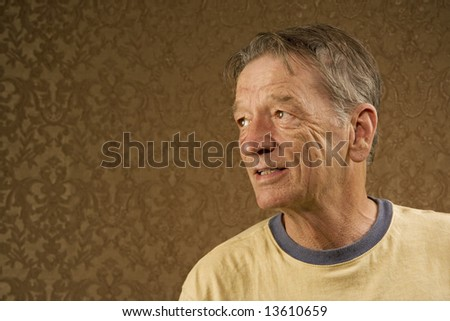 Man with a craggy face wearing a yellow shirt against a gold background with copy space