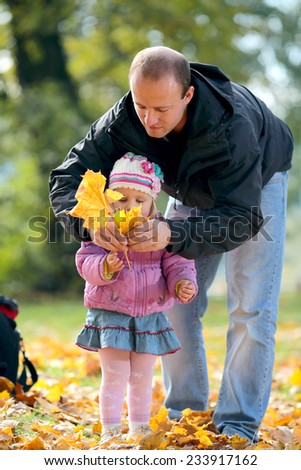 Man with a daughter collect fallen list in Park - stock photo