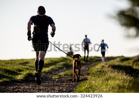 Man with a dog on a morning run - stock photo