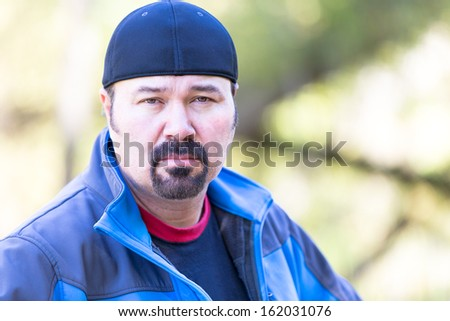 Man with a goatee looking determined attitude on a green sunny background