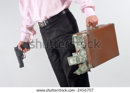 man with  a gun and case of dollars - stock photo