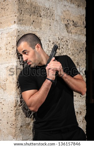 man with a gun in industrial place protect himself behind the wall - stock photo